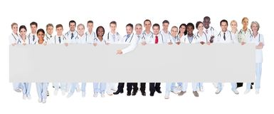 Multiethnic doctors holding blank banner. Portrait of multiethnic doctors holding blank banner against white background Royalty Free Stock Photos