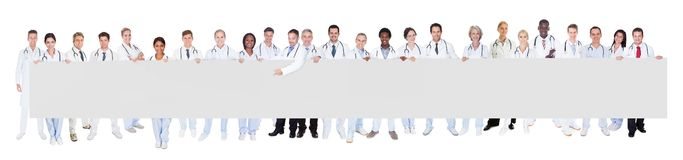 Multiethnic doctors holding blank banner. Portrait of multiethnic doctors holding blank banner against white background Stock Image
