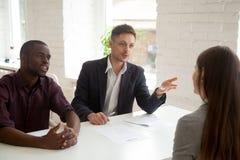 Employers talking to female employee considering her resume stock photo