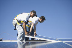 Multiethnic Engineers Placing Solar Panel Against Sky Royalty Free Stock Photography