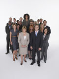Multiethnic Executives With Businesswoman Standing Taller. Portrait of multiethnic executives with businesswoman standing taller against white background royalty free stock photography