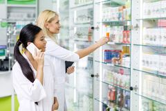 Multiethnic female pharmacists using digital devices while working. In drugstore royalty free stock photo