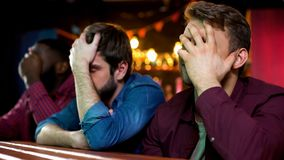 Multiethnic football fans making facepalm, disappointed with game loss, bar. Stock photo stock image