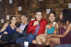Multiethnic Friends On Couch With Drinks Stock Photography