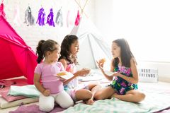 Friends Eating Donuts While Celebrating Pajama Party. Multiethnic friends eating donuts while celebrating pajama party at home stock images