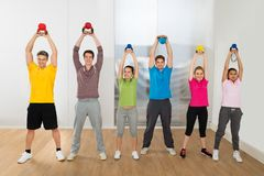 Multiethnic Friends Exercising With Kettle Bell. Group Of Multiethnic Friends Exercising With Colorful Kettle Bell stock photography
