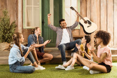 Multiethnic friends with guitar spending time together Stock Image