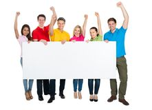 Multiethnic friends holding blank billboard cheering Royalty Free Stock Photos