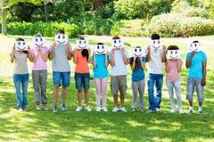 Multiethnic friends holding smileys in park Stock Photos