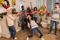 Multiethnic friends playing limbo game Stock Image