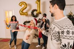 Multiethnic friends playing limbo game Royalty Free Stock Photos