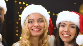 Multiethnic friends in santa hats holding champagne and looking to camera, pan. Stock footage stock video