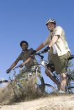 Multiethnic Friends Stand With Mountain Bikes On Hilltop. Low angle view of two multiethnic friends with mountain bikes on hilltop against clear blue sky Stock Photography