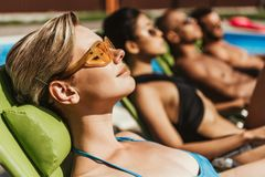 Multiethnic friends in sunglasses sunbathing on sunbeds at poolside. Selective focus royalty free stock images