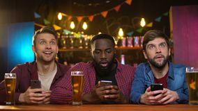 Multiethnic friends supporting favorite team, making bets for game result in pub