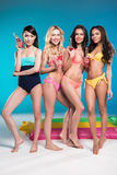 Multiethnic girls in swimwear posing and holding bottles with cocktails. Beautiful multiethnic girls in swimwear posing and holding bottles with cocktails Stock Photo