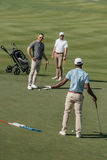 Multiethnic golfers talking during the game on green pitch at daytime. Young multiethnic golfers talking during the game on green pitch at daytime Stock Photos