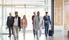 Multiethnic  group arrive at airport hall. International multiethnic businessmen group arrive at airport foyer Stock Photo