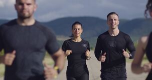 Multiethnic group of athletes running together on a panoramic countryside road. Diverse Team of joggers on morning