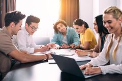 multiethnic group of business colleagues having discussion at table with graphs in modern royalty free stock photo