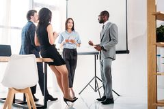 Multiethnic group of business people in formal wear discussing project together. In office royalty free stock photo