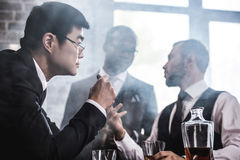 Multiethnic group of businessmen smoking and drinking whisky indoors Stock Photos