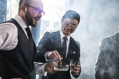 Multiethnic group of businessmen smoking and drinking whisky indoors Royalty Free Stock Photo
