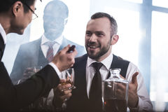 Multiethnic group of businessmen smoking and drinking whisky indoors Stock Image