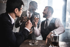 Multiethnic group of businessmen smoking and drinking whisky indoors. Multicultural business team royalty free stock photo