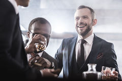 Multiethnic group of businessmen spending time together drinking whiskey and smoking. Multicultural business team royalty free stock photography