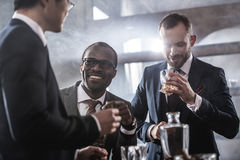 Multiethnic group of businessmen spending time together drinking whiskey and smoking Stock Photos