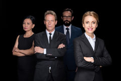 Multiethnic group of businesspeople standing with crossed arms and looking at camera isolated on black. Confident multiethnic group of businesspeople standing stock image