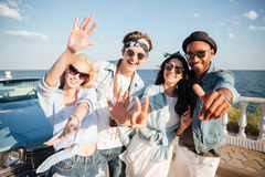 Multiethnic group of cheerful young people standing on promenade. In summer royalty free stock images