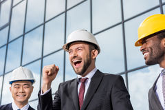 Multiethnic group of excited professional architects in helmets outside office building Royalty Free Stock Photography