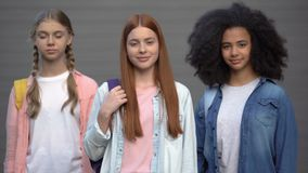 Multiethnic group of female students looking camera grey background, education. Stock footage stock video