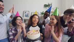 Multiethnic group of friends celebrating birthday singing blowing candle on cake stock video