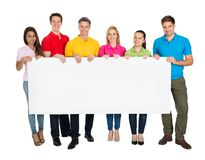 Multiethnic group of friends showing blank billboard. Happy Multiethnic Friends Showing Blank Billboard Isolated On White Background Royalty Free Stock Photo