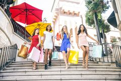 Beautiful women shopping. Multiethnic group of girls shopping - Four beautiful women having fun while buying some presents in a mall Stock Images