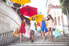 Beautiful women shopping. Multiethnic group of girls shopping - Four beautiful women having fun while buying some presents in a mall Stock Photography