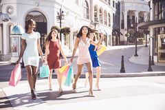 Beautiful women shopping. Multiethnic group of girls shopping - Four beautiful women having fun while buying some presents in a mall Royalty Free Stock Photo