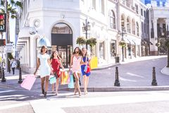 Beautiful women shopping. Multiethnic group of girls shopping - Four beautiful women having fun while buying some presents in a mall Royalty Free Stock Photography