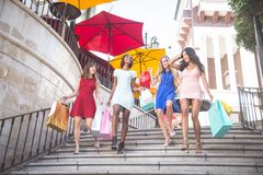 Beautiful women shopping. Multiethnic group of girls shopping - Four beautiful women having fun while buying some presents in a mall Stock Photos