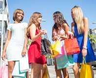 Beautiful women shopping. Multiethnic group of girls shopping - Four beautiful women having fun while buying some presents in a mall in Beverly Hills Stock Image
