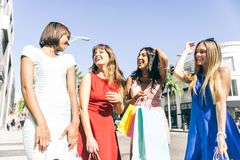 Beautiful women shopping. Multiethnic group of girls shopping - Four beautiful women having fun while buying some presents in a mall in Beverly Hills Royalty Free Stock Image