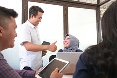 An attractive asian man congratulate his female hijab coworker for her success at the office stock image