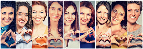 Multiethnic group of happy women making heart sign with hands. Multiethnic group of smiling cheerful happy women making heart sign with hands royalty free stock images