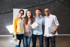 Multiethnic group of happy young business people standing in office. Multiethnic group of happy young business people holding tablet and laptop standing in stock photos