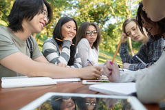 Multiethnic group of happy young students. Image of multiethnic group of happy young students sitting and studying outdoors while talking. Looking aside Royalty Free Stock Photos