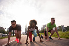 Multiethnic group of people on start position for jogging. Multiethnic group of people on start position for morning  jogging with urban backgrond Royalty Free Stock Image