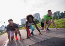 Multiethnic group of people on start position for jogging. Multiethnic group of people on start position for morning  jogging with urban backgrond Royalty Free Stock Photo